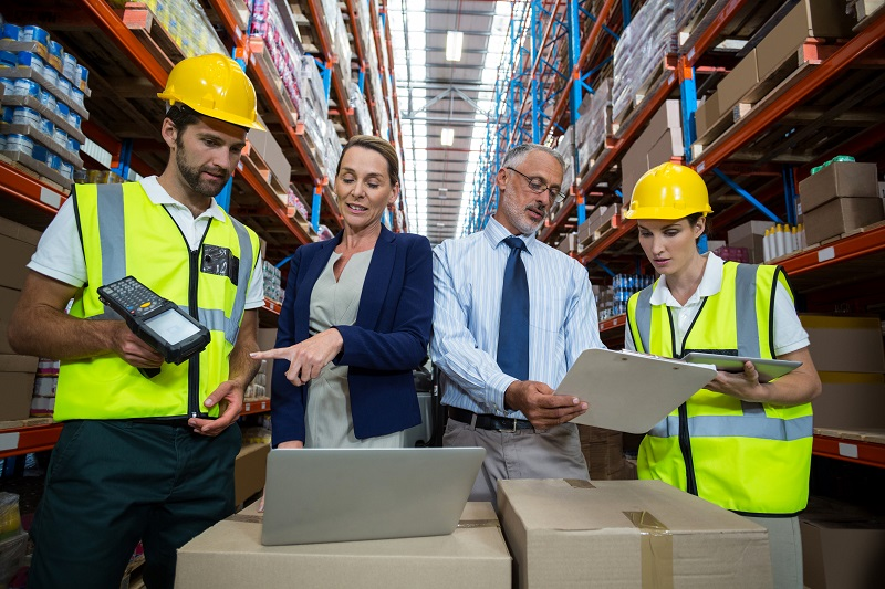 Warehouse manager and client interacting with co-workers in warehouse