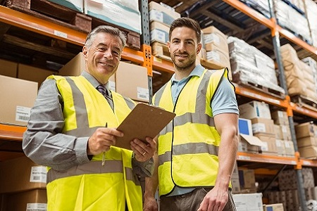 Warehouse manager and foreman looking at camera in a large warehouse